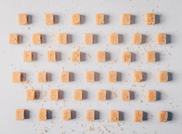 Brown sugar cubes lined up. flat lay. Free Photo
