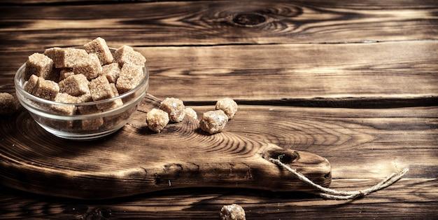 木製のテーブルの上のカップの黒糖。 Premium写真