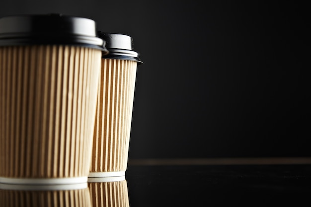 Brown take away paper cups closed with caps isolated on left Free Photo