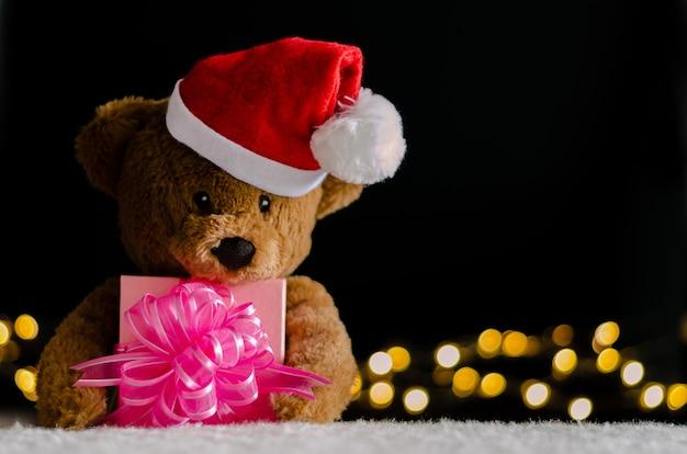 Коричневый плюшевый мишка в шляпе санта-клауса держит частичный фокус рождественской подарочной коробки. Premium Фотографии