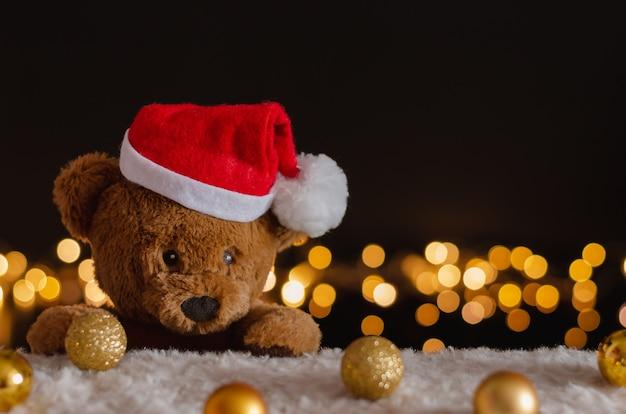 Коричневый плюшевый мишка в шляпе санта-клауса с рождественскими украшениями и фоном огней. Premium Фотографии