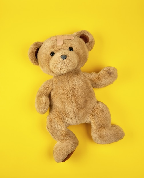 Brown teddy bear on yellow Premium Photo