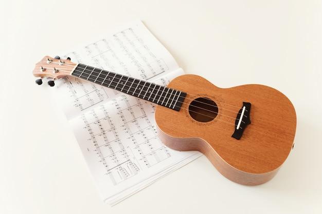 Brown ukulele guitar, sheet music. top view Premium Photo