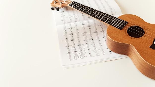 Brown ukulele guitar, sheet music. Premium Photo