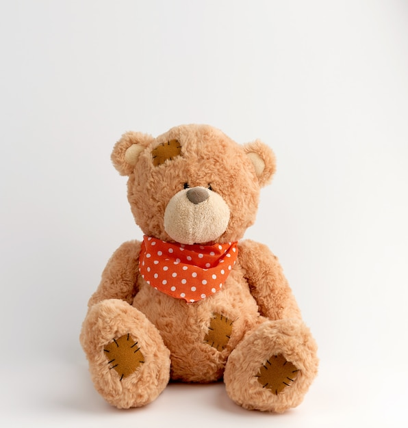 Brown vintage teddy bear with patches, white background Premium Photo