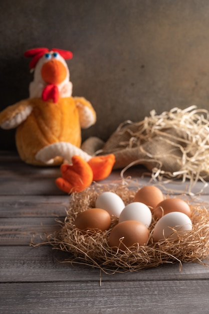 Brown and white chicken eggs in a straw nest on wooden background. next to a chicken toy. rustic style. copy space Premium Photo