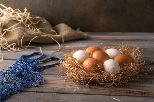 Brown and white chicken eggs in a straw nest on wooden background next to eco string bag rustic style copy space Premium Photo