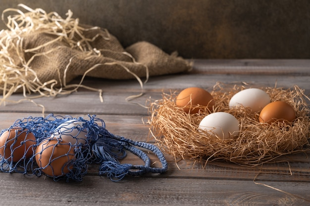 Brown and white chicken eggs in a straw nest on wooden background. next to eco string bag with eggs. rustic style. copy space Premium Photo