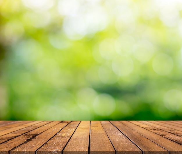 Brown wood surface with a green blurred background Premium Photo