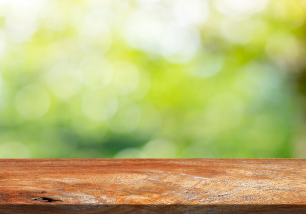 Brown wood table top on a green bokeh blur background . Premium Photo