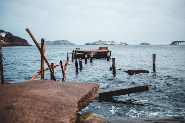 昼間の海の茶色の木製ドック 無料写真