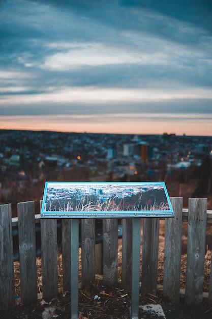 日没時に水の体の近くの茶色の木製フェンス 無料写真