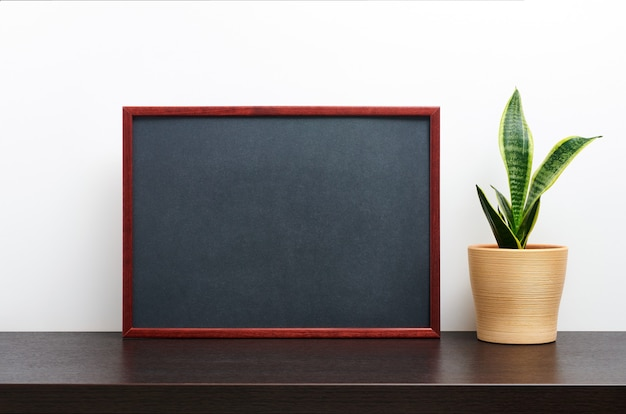 어두운 작업 공간 테이블과 흰색 배경에 냄비에 선인장과 가로 방향으로 갈색 나무 프레임 또는 칠판 모형 프리미엄 사진