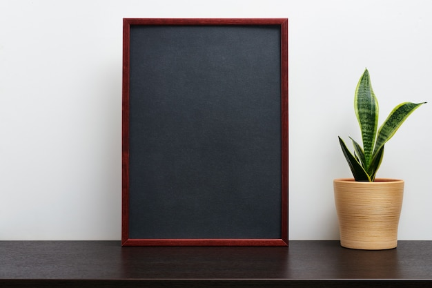 어두운 작업 공간 테이블과 흰색 배경에 냄비에 선인장과 세로 방향으로 갈색 나무 프레임 또는 칠판 모형 프리미엄 사진