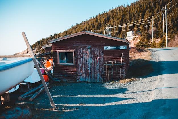 昼間に緑の木々の近くの茶色の木造住宅 無料写真