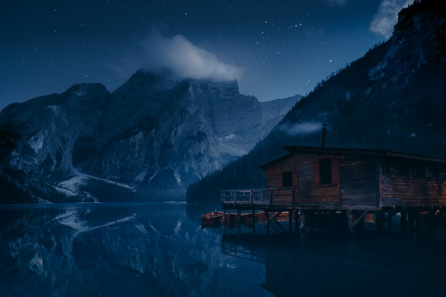 산 근처 호수에 갈색 목조 주택 무료 사진