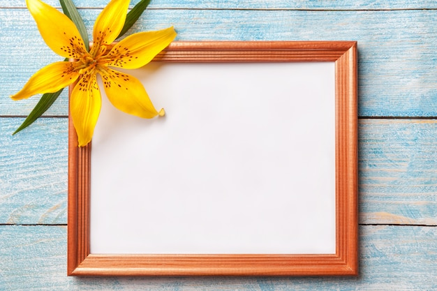 Brown wooden photo frame with yellow flowers lily on old blue shabby background. Premium Photo