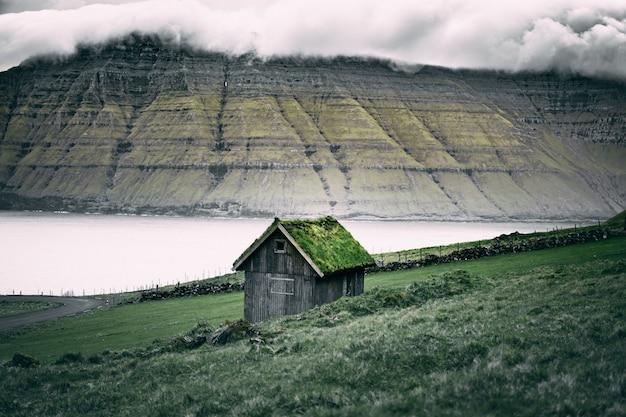 Tettoia in legno marrone con erba sul tetto sopra le scogliere di roccia Foto Gratuite