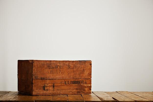 白い壁のあるスタジオの木製のテーブルに黒い文字で茶色の着用素朴なボックス 無料写真