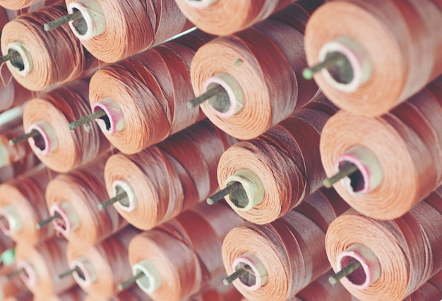Brown yarn cone mounted in a fabrics factory. Premium Photo