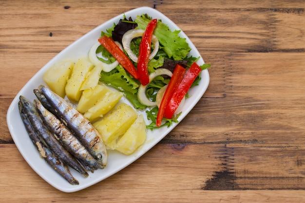 Brownでたジャガイモとサラダ茶色の木製の白い皿に揚げ Premium写真