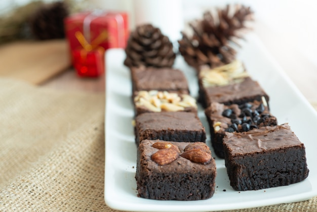Brownie chocolate cake on white plate, with christmas decoration background Premium Photo