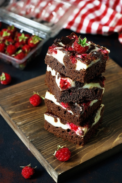 Brownies tower with cottage cheesecake and raspberries Free Photo