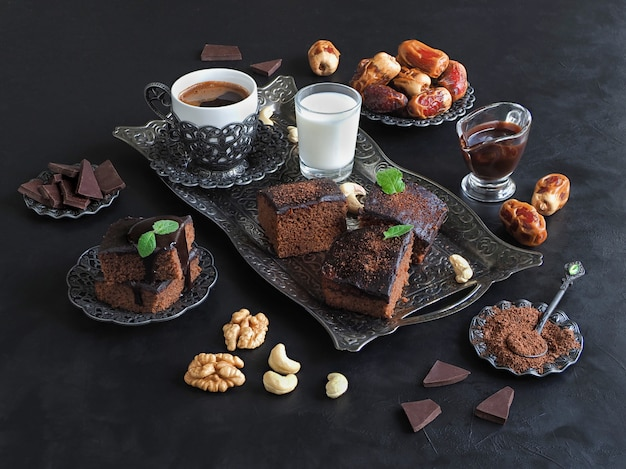 Premium Photo | Brownies with dates, milk and coffee are laid out on a  black surface. festive ramadan background