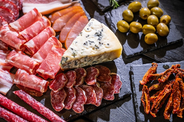 Brunch. appetizers table with various of cheese, curred meat, sausage, olives, nuts and fruits. festive family or party snack concept. Premium Photo