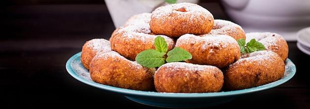 ブランチまたはランチ。粉砂糖をまぶした自家製ドーナツ。 無料写真