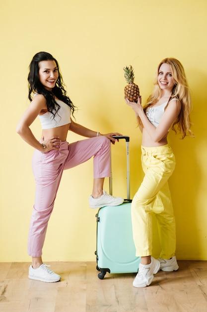Брюнетка и блондинка в красочные брюки на желтой стене. розовый и желтый цвет. путешествие с мятным чемоданом и ананасом. Premium Фотографии