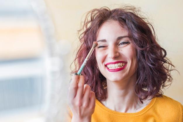 Brunette blogger doing her make up Free Photo