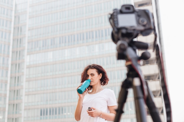 Brunette blogger drinking water from a bottle Free Photo