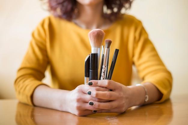 Brunette blogger showing make up brushes Free Photo