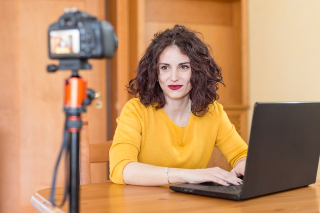 Brunette blogger writing on the laptop Free Photo