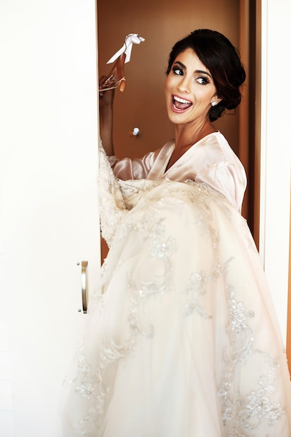 Brunette bride in silk robe stands with wedding dress in her arms Premium  Photo 7b9c8d5ef