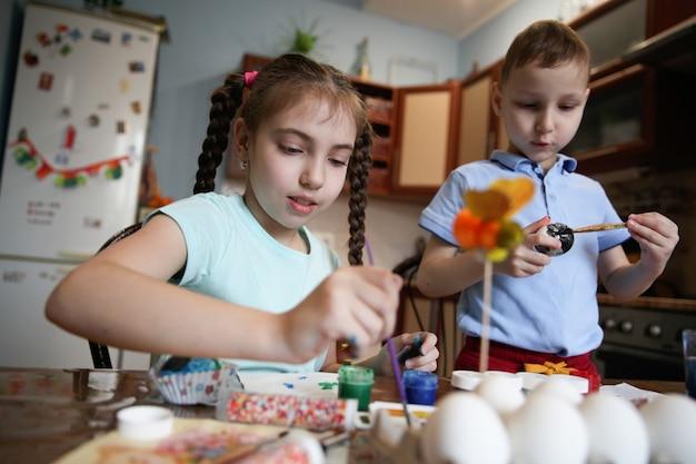 갈색 머리 형제와 자매는 부엌에서 집에서 테이블에 앉아 부활절 달걀을 장식 프리미엄 사진