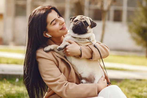 Brunette in a brown coat walks with pug Free Photo