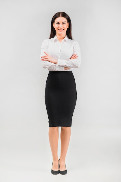 Brunette business woman standing with crossed arms Free Photo