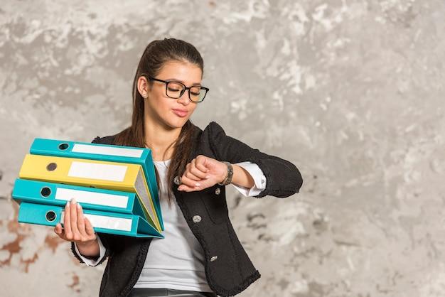 Brunette businesswoman holding folders Free Photo