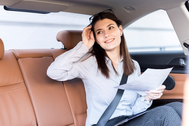 Brunette businesswoman posing inside a car Free Photo