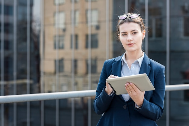 Brunette businesswoman posing with a tablet Free Photo
