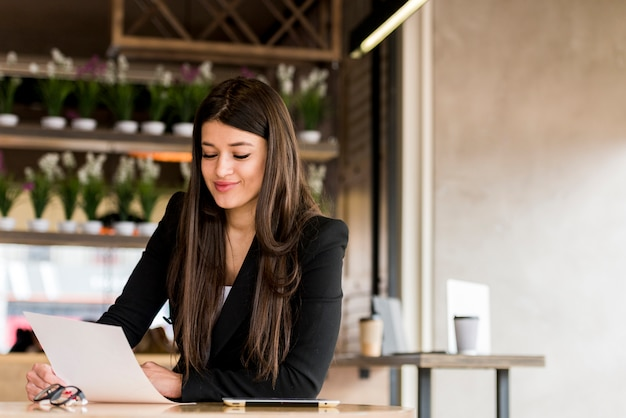 Brunette businesswoman reading document Free Photo