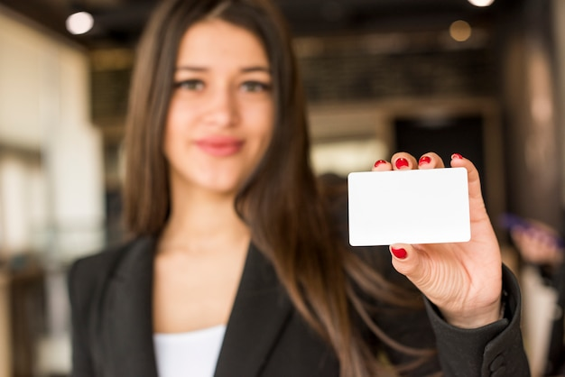 Brunette businesswoman showing card Free Photo