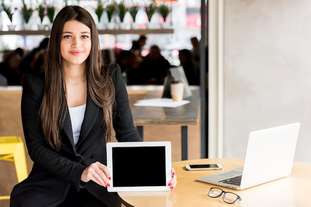 Brunette businesswoman showing her tablet Free Photo