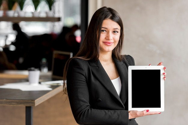 Brunette businesswoman showing tablet Free Photo