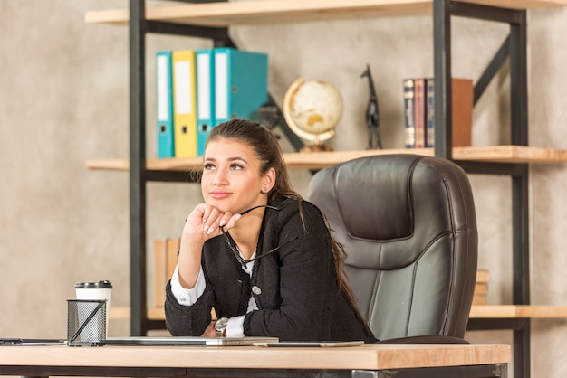 Brunette businesswoman thinking at her office Free Photo