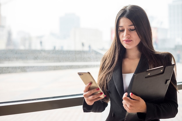 Brunette businesswoman using her mobile phone Free Photo