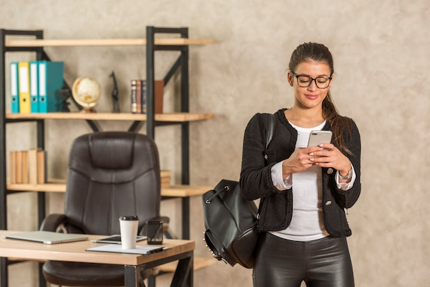 Brunette businesswoman using her smartphone Free Photo