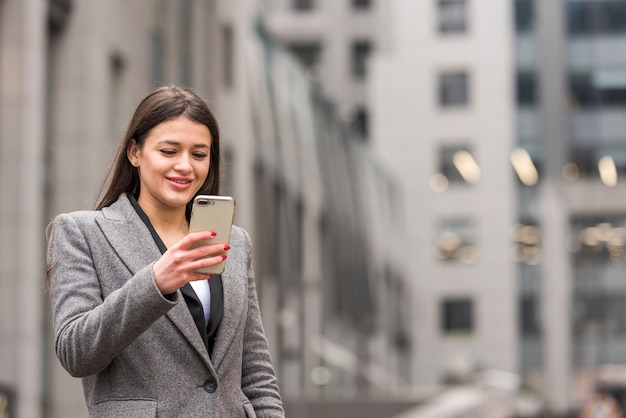Brunette businesswoman using her smartphone Free Photo
